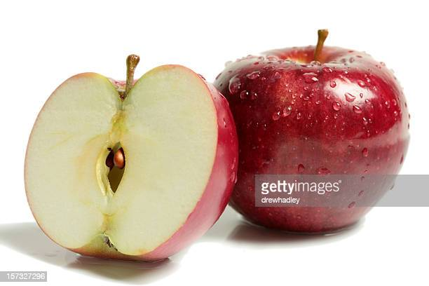 Two rosy red apples with one halved on white surface