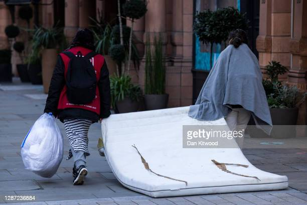 Two rough sleepers drag at mattress down the road in Mayfair on November 23, 2020 in London, England.