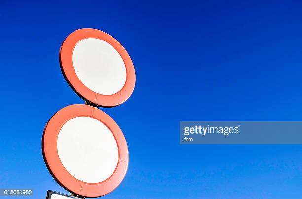 Two round empty street signs with blue sky