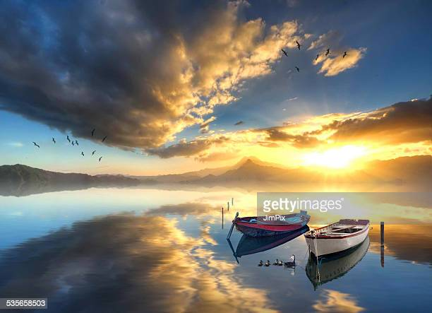Two rowboats anchored in calm sea at sunrise