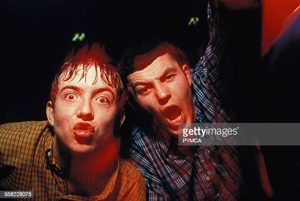 Two rowdy northern lads with gelled hair and chequered shirts pose in club Manchester UK 1999