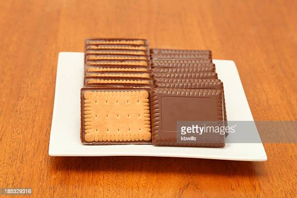 two rows of chocolate biscuits cookies on square white plate