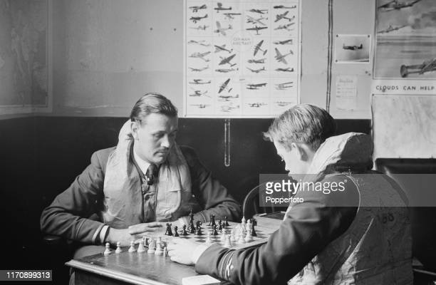 Two Royal Air Force fighter pilots play a game of chess in a rest room as they stand by for their instructions at a RAF Fighter Command station in...