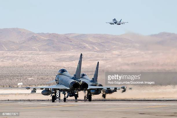Two Royal Air Force Typhoon fighters await takeoff clearance at Nellis Air Force Base.