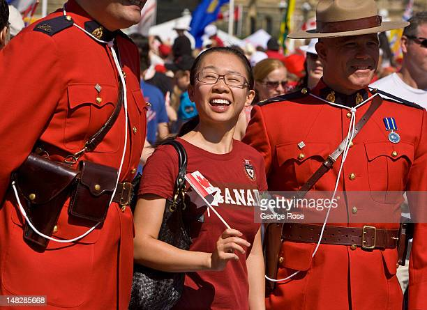 Two Royal Canadian Mounted Police officers pose for pictures as thousands gather on Parliament Hill to celebrate Canada Day on July 1 2012 in Ottawa...