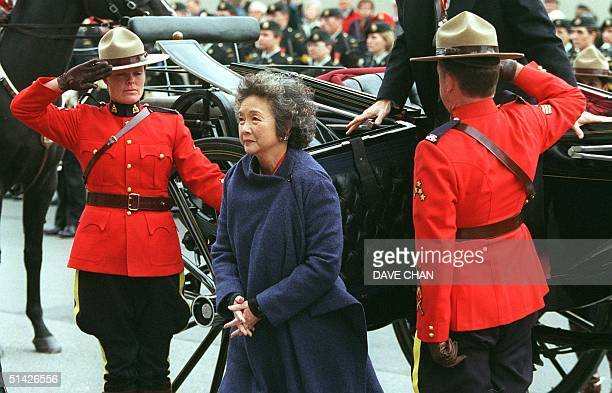Two Royal Canadian Mounted Police officers salute as Canadian Governor General Adrienne Clarkson arrives on Parliament Hill 12 October to deliver her...
