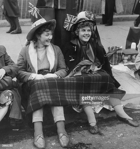 Two royal fans with union jacks in their hats have a kerb side seat for the wedding of Princess Margaret and Antony Armstrong Jones.