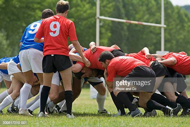 Two rugby teams in scrum on pitch