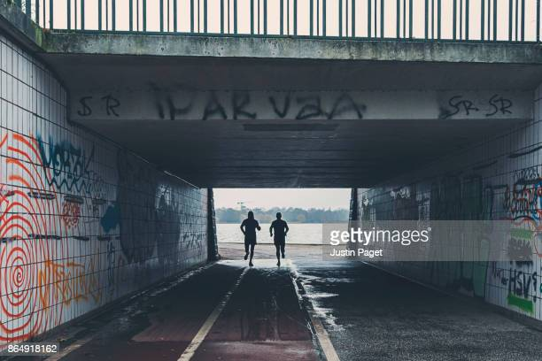 Two runners in underpass