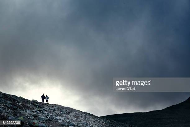 Two runners mountain running with dramatic sky