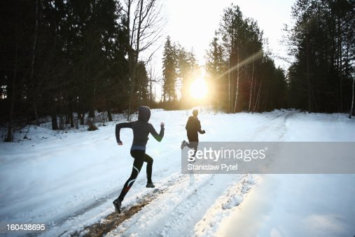 Two runners on snowy forest road in the morning