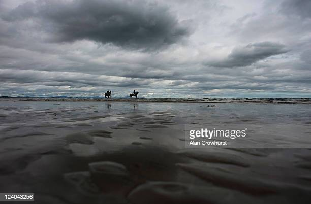 Two runners take a dip in the Irish Sea before racing during the Laytown race meeting run on the beach on September 08 2011 in Laytown Ireland