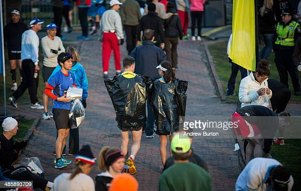 Two runners walk with garbage bags on to keep them warm prior to running the Boston Marathon on April 21 2014 in Boston Massachusetts Today marks the...