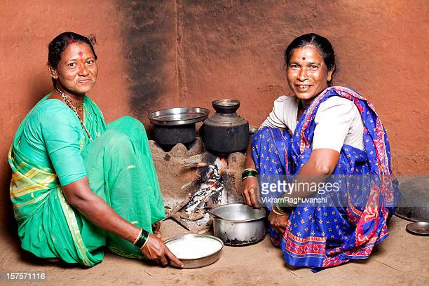 Two Rural Indian Women Females cooking food in the Kitchen