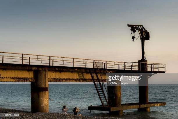 Two Russian girls sitting under the remnants of a loading station for cruise ships doing tours in the Black Sea during Soviet times Abkhazia is a...