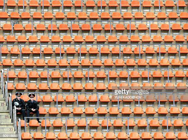 Two Russian policemen guard empty stadium's stand during the warmup football match of Russian national team against a selection of foreigners playing...