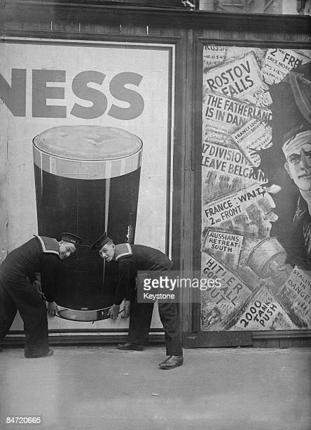 Two sailors demonstrate wishful thinking with a Guinness poster in London 14th September 1942