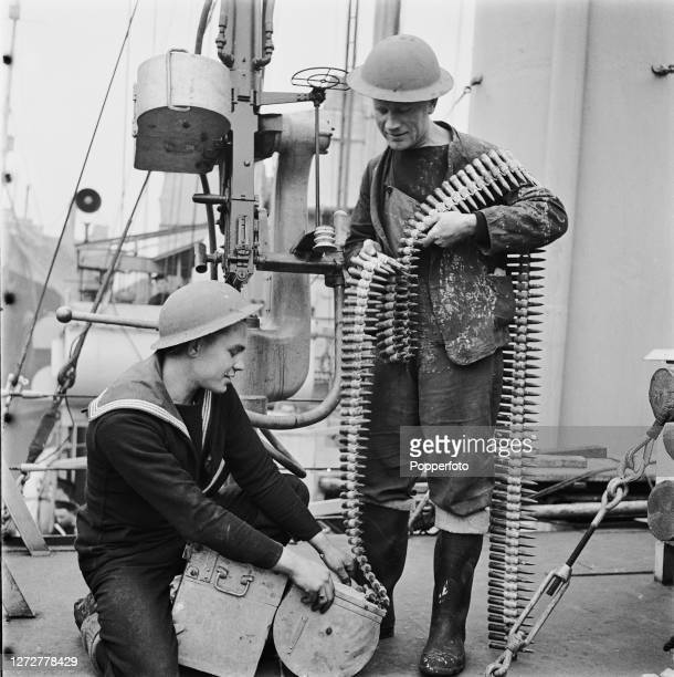 Two sailors fill a cartridge drum with a belt of ammunition for an antiaircraft autocannon aboard a United States Navy destroyer transferred to the...