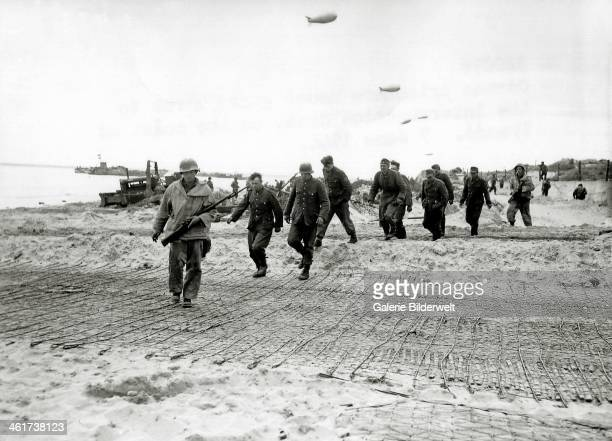 Two sailors from the 2nd Naval Beach Battalion of the 1st Engineer Special Brigade escort a group of eight German prisoners June 1944 Barrage...