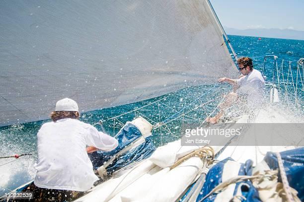 Two sailors preparing a sail during a race