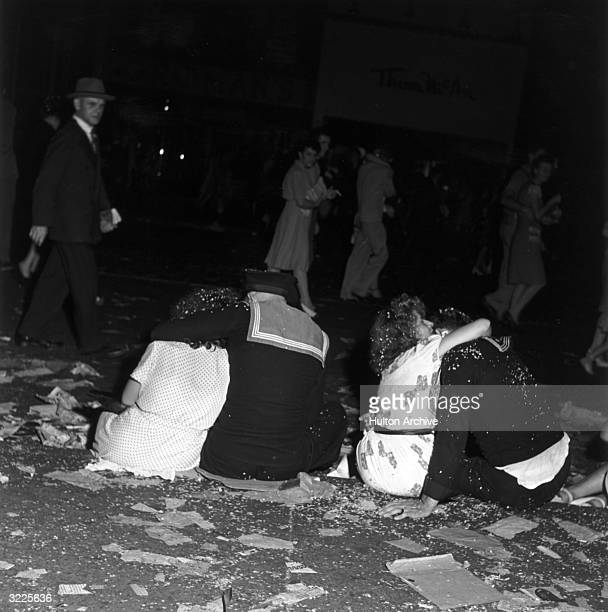 Two sailors sit on a curb with their backs to the camera hugging two women while passing civilians watch during VJ Day celebrations