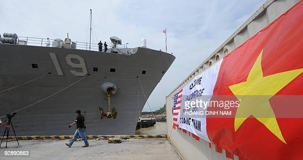 Two sailors stand on the top deck of the USS Blue Ridge anchored near to a banner reading Welcome to USS Blue Ridge and USS Lassen hung on a...