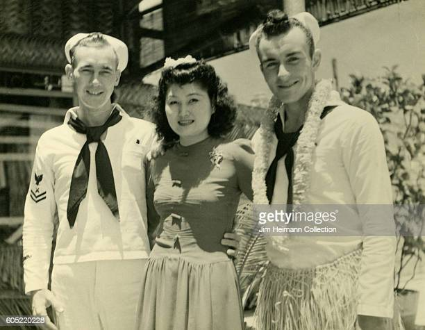 Two sailors standing outside with woman. One sailor is wearing a lei and a grass skirt.