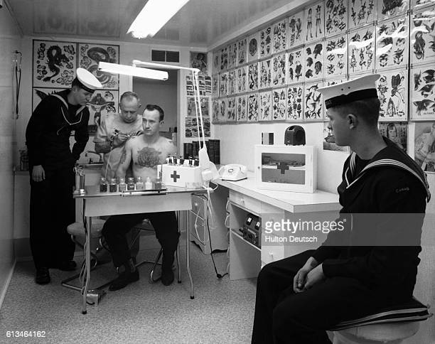 Two sailors watch as tattooist Forbes A Hendry adds some decorations to the skin of exnavy man Joe Williams
