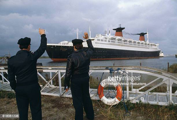 Two sailors wave as the French ocean liner Norway leaves Le Havre harbor in the Seine Bay The ocean liner was formerly named France