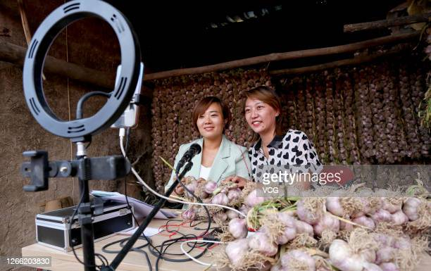 Two saleswomen sell garlic as they live stream video on a smartphone at Wuzhuang village on August 13, 2020 in Zhangye, Gansu Province of China.