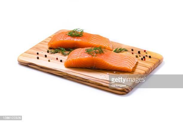 due filetti di salmone su un tagliere isolato su sfondo bianco - salmone frutto di mare foto e immagini stock