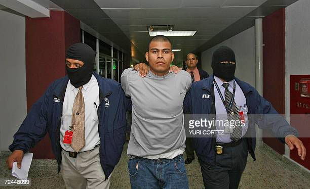 Two Salvadorean Interpol officers lead Juan Elias Rodriguez Luna a member of youth gang 'MS' upon his arrival at the international airport in...