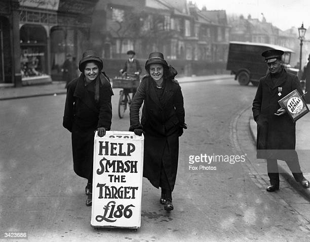 Two Salvation Army ladies with a sign encouraging people to donate money during self denial week