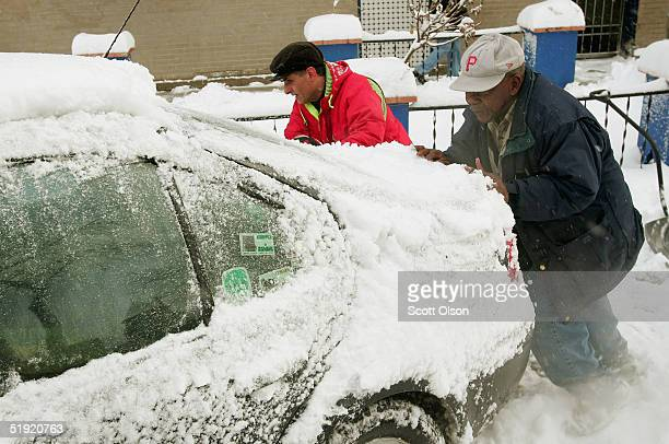 Two samaritans help to push a stranded motorist from a parking spot January 6 2005 in Chicago Illinois About 10 inches of snow was dumped on the city...