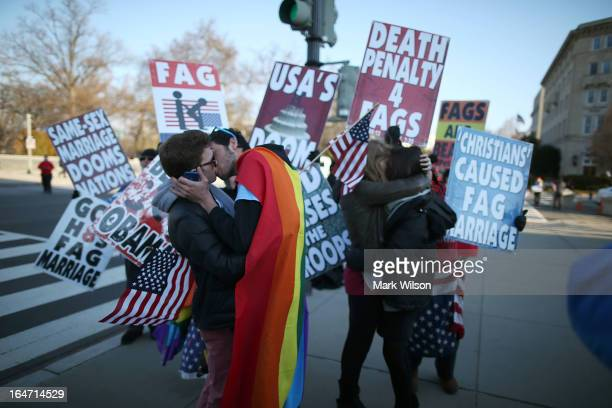 Two same sex couples kiss in front of Westboro Baptist Church protesters at the US Supreme Court on March 27 2013 in Washington DC Today the high...