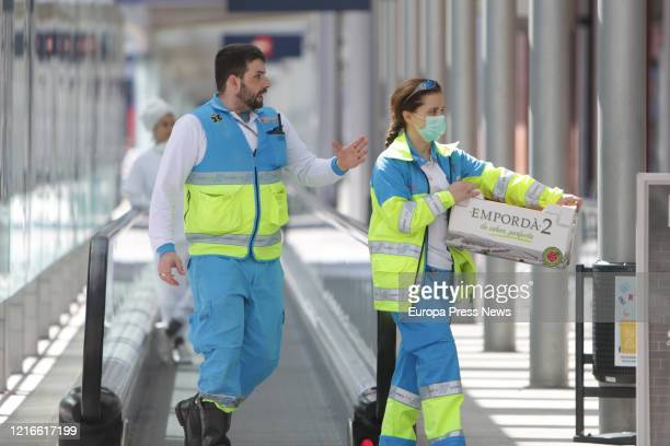 Two sanitary workers are seen carrying material at he campaign hospital of IFEMA established to help during the infection admitting coronavirus...