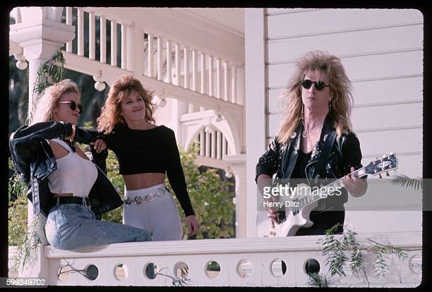 Two scantily clad groupies admire a guitarist of the band Great White Great White was one of the many heavy metal hair bands of the late 1980s