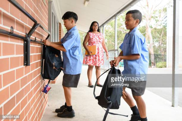 Two school boys hanging backpacks up on pegs wall outside school