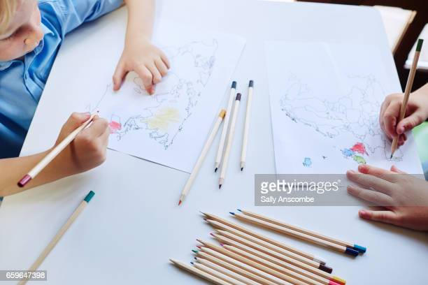 two school children doing school work - colouring stock pictures, royalty-free photos & images
