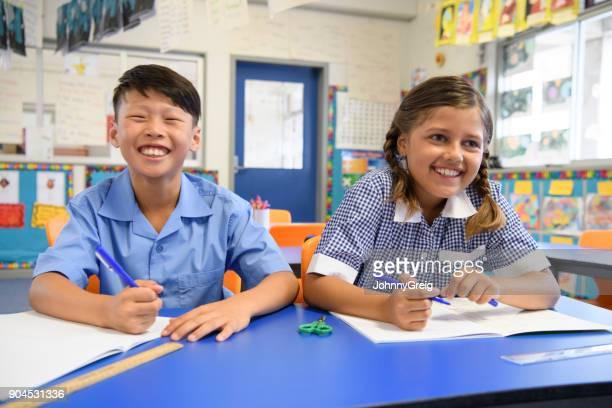 教室と笑顔で隣同士に座っている 2 つの学校の子供たち