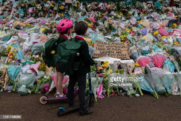 Two school children stop to look at floral tributes left at Clapham Common bandstand where people continue to pay their respects to Sarah Everard on...
