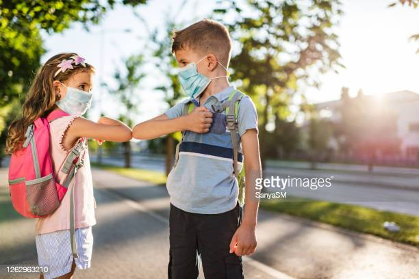 two school children using elbow bump as an alternative handshake outdoors in nature - elbow bump stock pictures, royalty-free photos & images