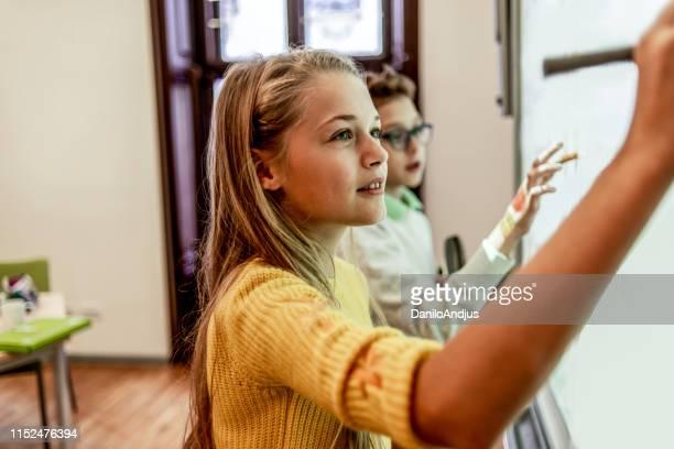 due compagni di scuola utilizzando la scheda intelligente per il loro progetto - educazione primaria foto e immagini stock