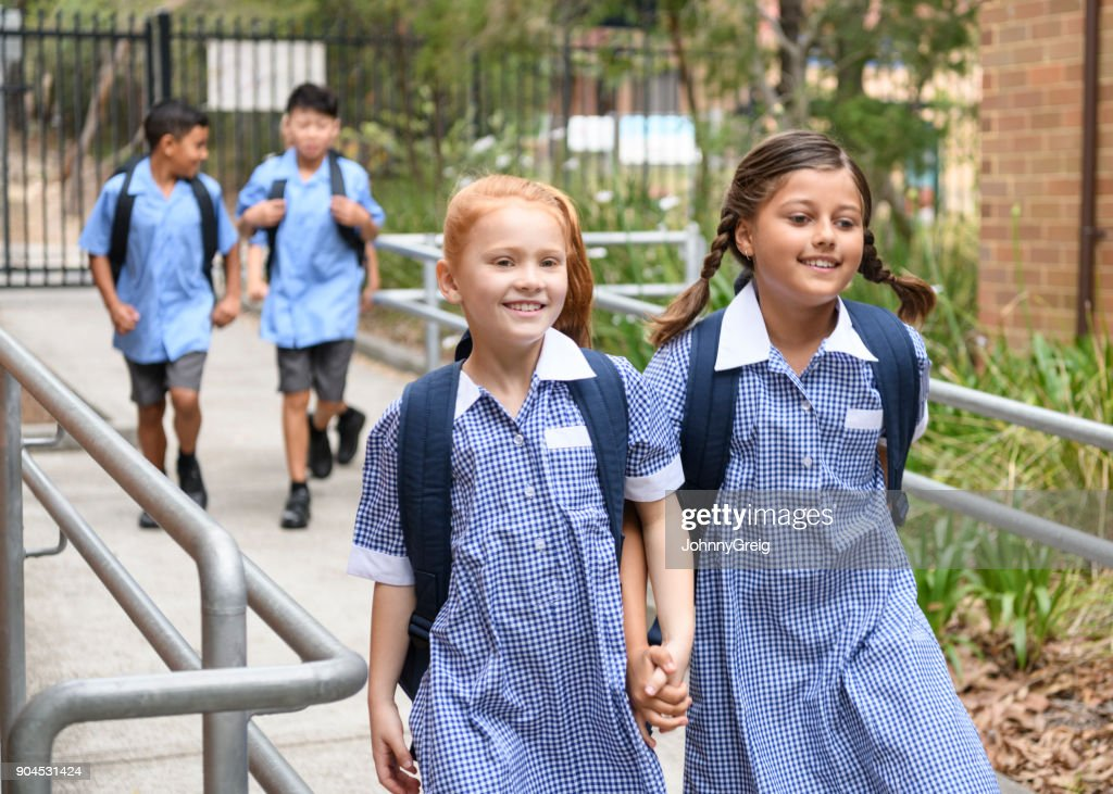 Two school girls holding hands on way to school : Stock Photo