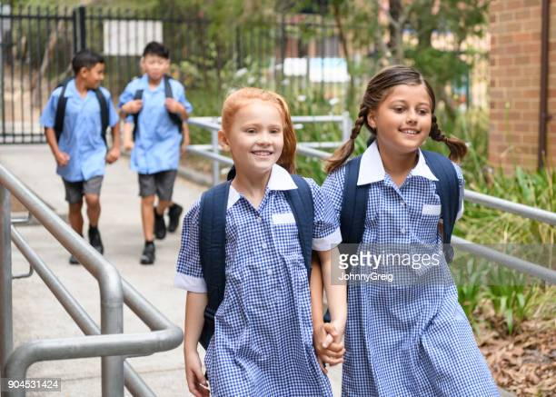 Two school girls holding hands on way to school