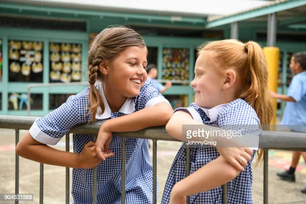 Two school girls leaning on railings in playground and chatting