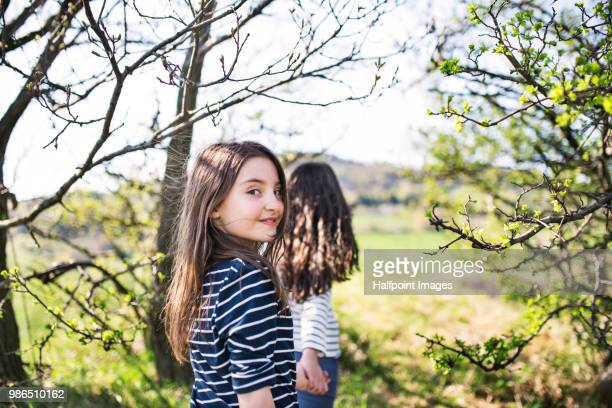 Two school girls on a walk in spring nature.