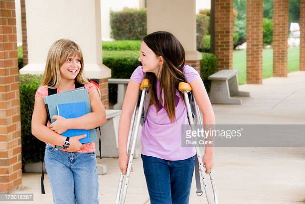 Two school girls, one carries books for her injured friend