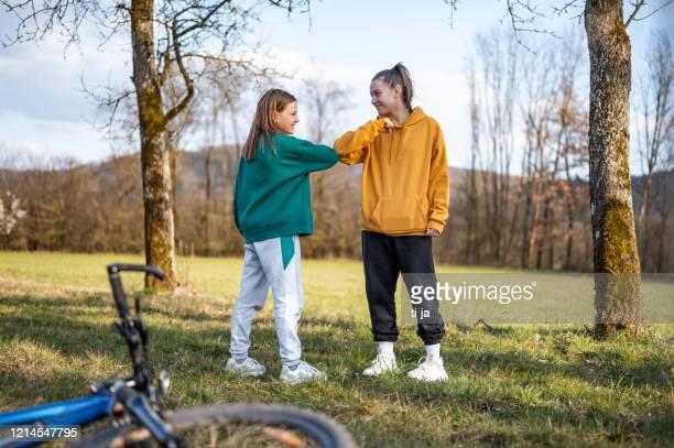 zwei schulmädchen mit ellbogenstoß als alternativer handschlag im freien in der natur - jugendkultur stock-fotos und bilder
