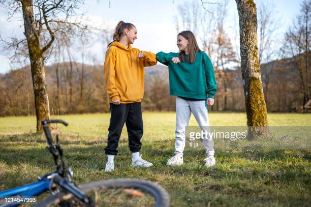 two school girls using elbow bump as an alternative handshake outdoors in nature - elbow bump stock pictures, royalty-free photos & images